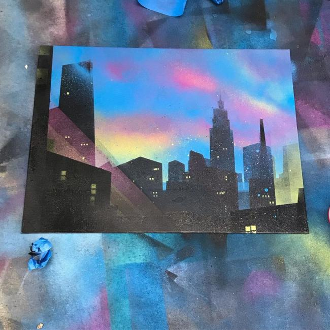 Spray paint on canvas painting of a city at dusk